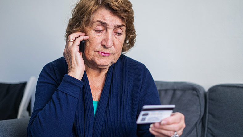 A woman reads her bank card while using the phone.