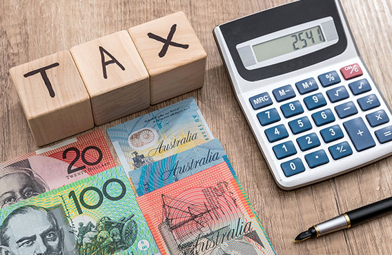 Blocks which spell out TAX, a calculator, pen and Australian money placed on a table