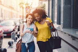 Two women walking down a city street looking at something on a phone