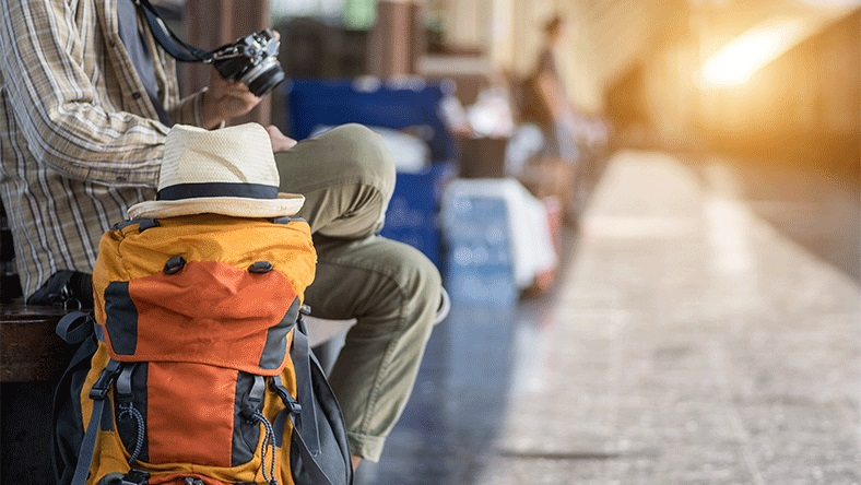 A man waiting at a train station with a large backpack and camera.