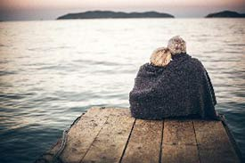 Senior couple sitting on the edge of a pier with a blanket around them