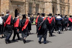 University students marching down the street in graduation robes and gowns