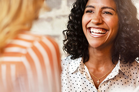 Woman smiles in conversation. This article answers questions about mutual banking.