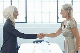Two women shaking hands and smiling with table and window in the background