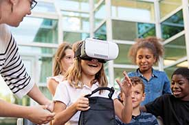 Excited group of children standing around little girl wearing goggles, while teacher assists