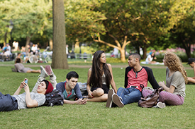Group of university student lazing about outdoors on campus