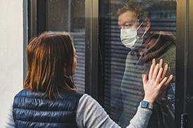 A man in a medical mask holds his hand to a woman through a window, practicing caremongering.