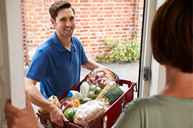 Man delivering box of fruit and vegetables to woman as part of food subscription service.