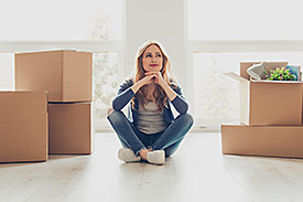 Satisfied woman sitting in an empty room with boxes packed