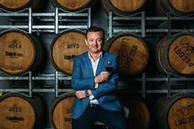 Picture of Luke Mangan standing in front of wine barrels with a glass of red wine