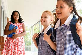 Two children wearing backpacks, looking excited in school environment with teacher in a pink dress watches on