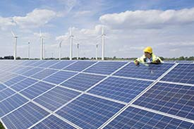 Worker wearing high visibility work wear climbing on a roof covered in solar panels in front of a wind farm
