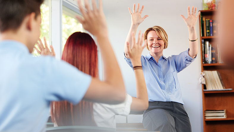 Teacher at front of a class room encouraging students to raise their hands.
