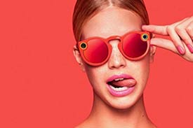 Female model wearing snapchat spectacles (glasses with cameras) against a peach background