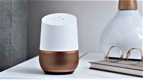 Google home sitting on a bedroom sidetable with lamp, book and glasses in view