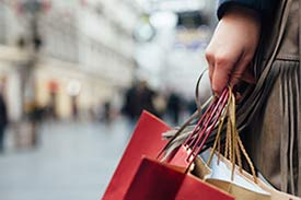 woman on an outside shopping strip holding shopping bags