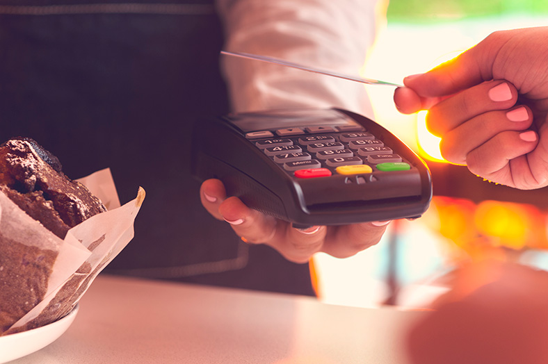 Person's hand ready to tap credit card on eftpos machine being held by business representative