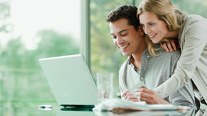 Couple planning solutions to their debt problems using laptop.
