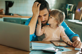Father with daughter at computer worrying about expenses over the holiday period