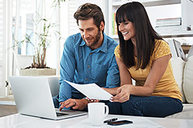 Smiling couple look at laptop