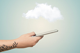 A person with a tattoo on forearm holds out a mobile phone while the foreground is made up of a single cloud and blue sky