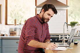 Man with beard sitting in kitchen holding a pen and writing on a piece of paper with laptop and phone nearby