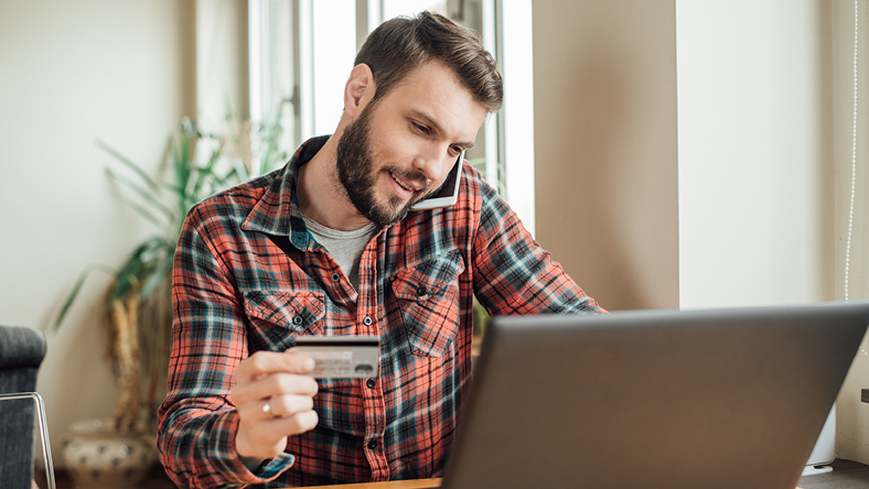 man researching on a laptop while looking at a credit card