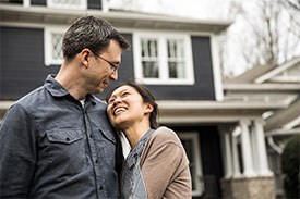 Woman embracing man outside in front of home