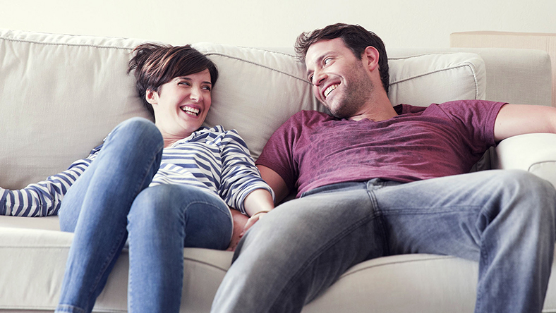 A happy pair of first home buyers lounge on the couch and smile at each other. 5 must read tips for first home buyers.