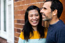 Couple standing in front of brick home smiling