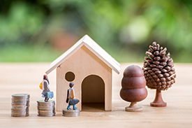 Small male and female figurines outside a miniature home made out of wood