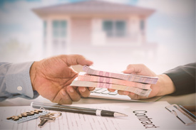 Cash changes hands over a contract - Lenders Mortgage Insurance allows home buyers to make a smaller deposit.
