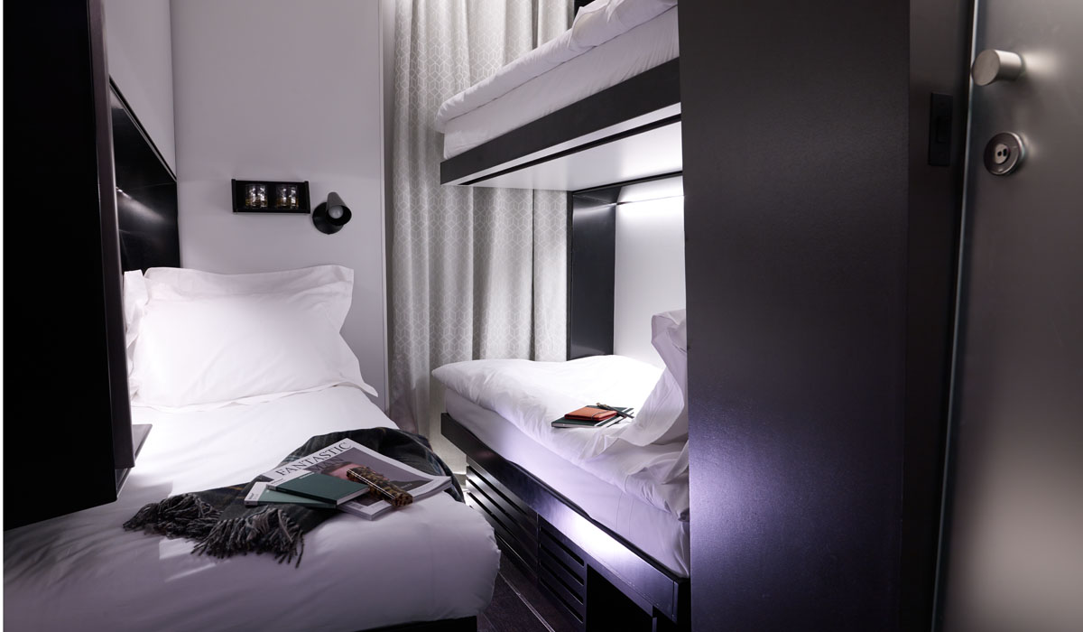 Micro hotel room with bunk beds with built in lighting, constructed from shipping containers