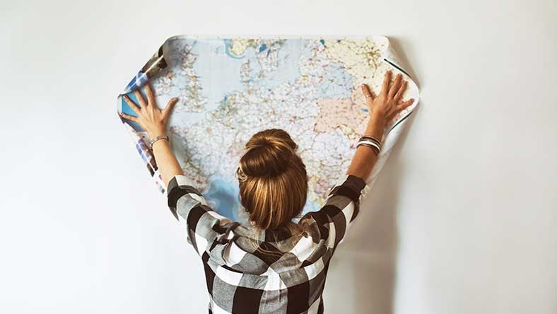 Young women spreading out a global printed map on the wall