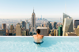 Man in pool, looking out at city view