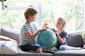 Young boy and girl sitting on a couch and looking at a globe of the world