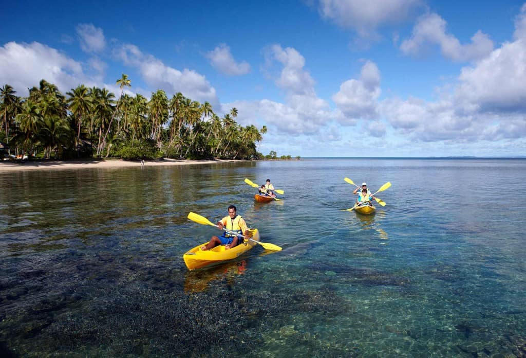 Three people kayaking in single kayaks across a coral reef near the shore of Fiji