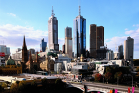 A picture of Melbourne, Victoria showing Flinders Street Station, a bridge crossing the Yarra River, Federation Square and some iconic buildings