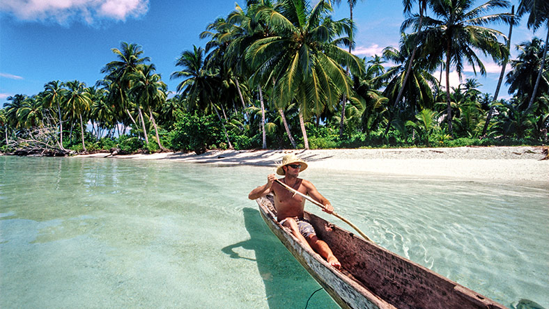 Man on holiday in Indonesia paddling in a long tail boat on a tropical beach.