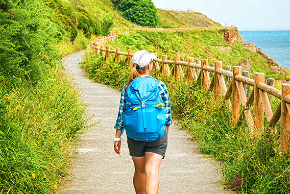 A woman hiking in warm weather near the coast with a blue backpack and cap